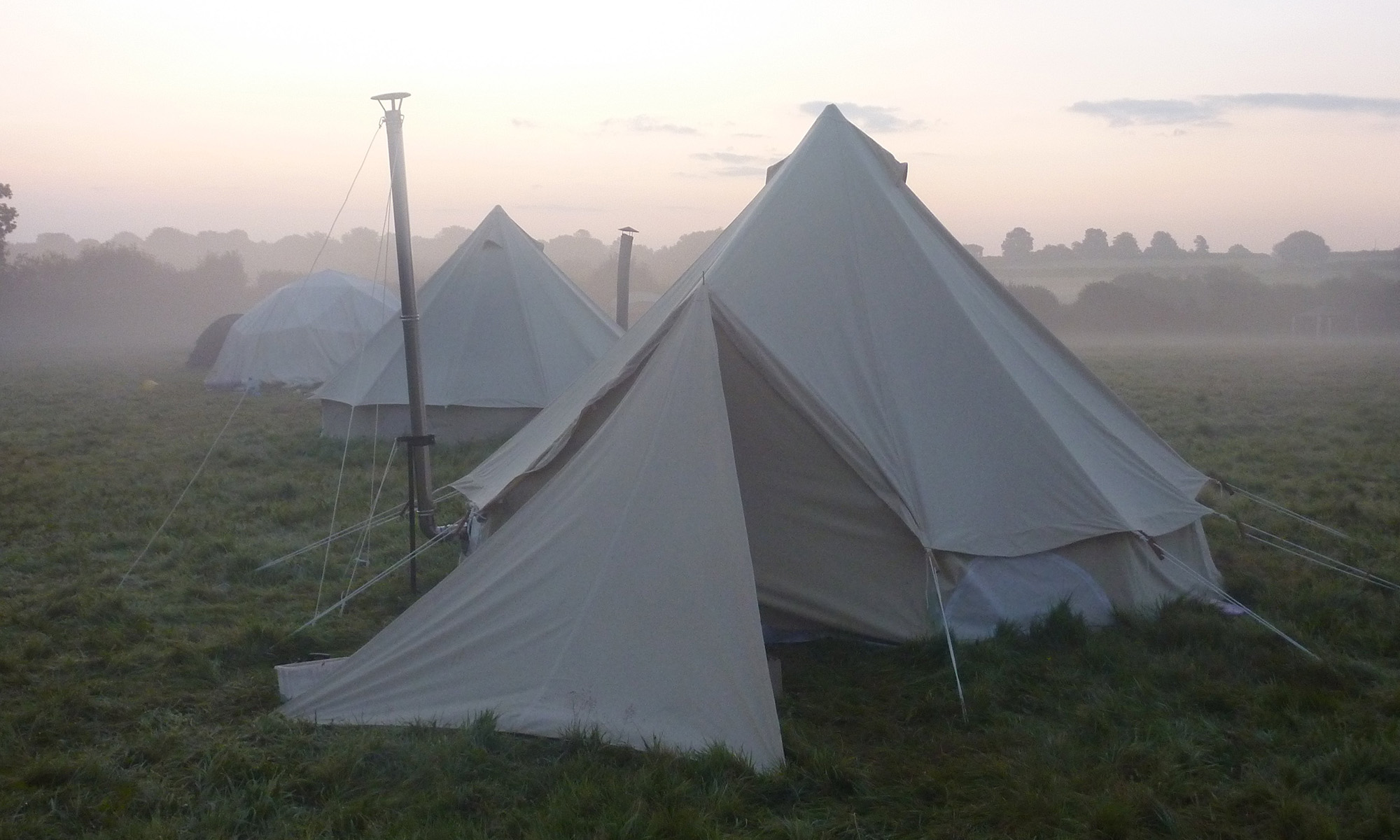 A bell tent in the foreground with other tents and domes in the background. It's dawn and misty at Queer Pagan Camp